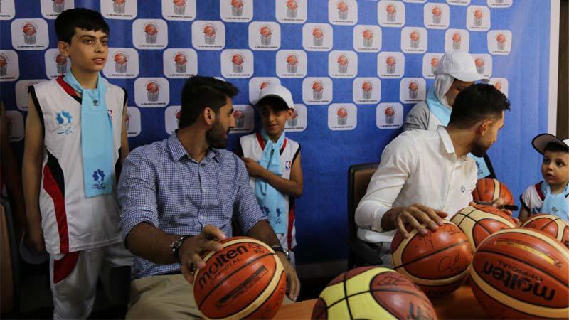 اعضاء تیم ملی بسکتبال ایران در حال امضاء توپ برای هدیه به کودکان بنیاد نیکوکاران راه آسمان